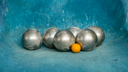 Shiny Metal Petanque Balls and Yellow Wooden Ball on Blue/ Teal Plastic Chair - Scratching Texture. Complementary color scheme