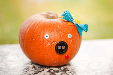 A humorous Halloween pumpkin with buttons and ribbons that looks like a pig.