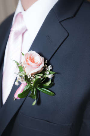 The groom wears a touch of the bride`s chosen color of pink by wearing a coordinating tie, shirt and rose boutonniere.
