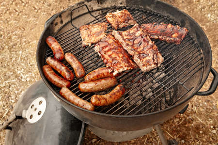A small outdoor grill fueled by glowing charcoal briquettes browns and sears an assortment of sausages and baby back ribs.