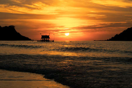 Silhouetted ship on a background of golden sunset. Sunset, Philippines. On the seashore.