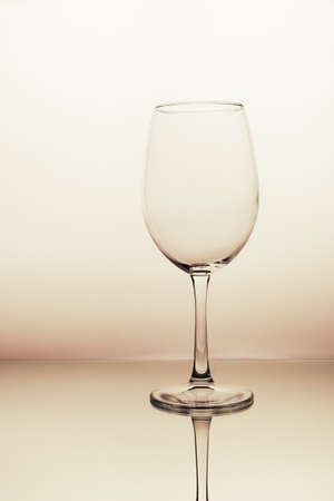 wine empty glasses on soft beige background. Vertical. Reflection in the mirror.