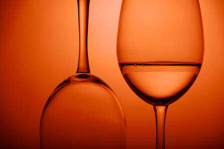 close-up two wine glasses on orange background. Horizontal. One glass upside down.