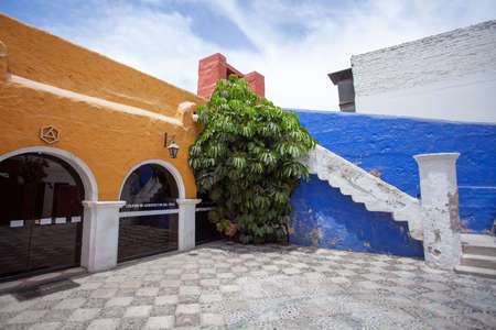 Courtyard in the monastery of Santa Catalina, Arequipa, Peru, the walls are yellow and blue, a tree grows in the center