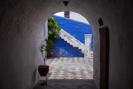 View from the arch into the courtyard of the blue and white wall and steps Santa Catalina, Arequipa, Peru