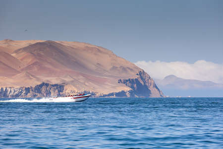 A speed boat carries tourists on an excursion to the island of Ballestas, the Ica region, Peru. Copy paste