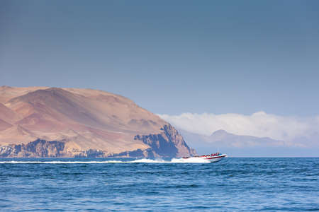 Boat at high speed carries tourists on an excursion to the Ballestas island, Region Ica, Peru. Copy past Stock Photo