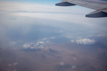 The view from the airplane window on the mountains in the clouds