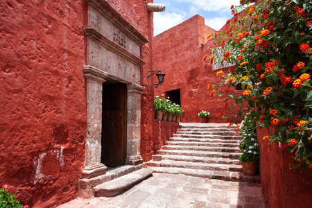 Narrow street with the arch of the monastery of Santa Catalina, Arequipa, Peru, potted flowers around