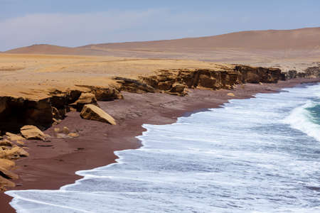 Paracas National Reserve, red sand beach, view of the ocean waves and sea foam.
