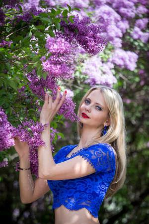 Beautiful blonde near a lilac in a blue top. Vertical orientation