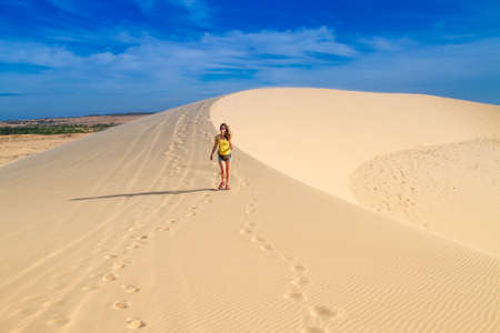 Woman walking along the crest of a dune, alone
