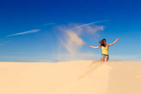 Woman in a yellow top in the desert against the blue sky