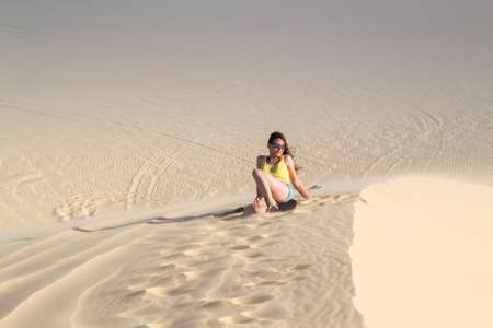 Woman sitting on the sand in the desert Banque d'images