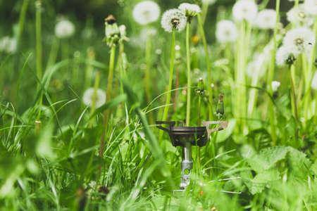 Tourist burner in grass and dandelions.