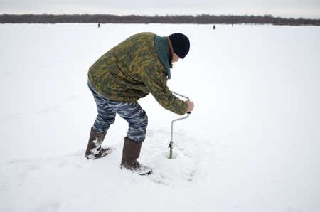 valenki: winter fisherman drill the hole in the river Stock Photo