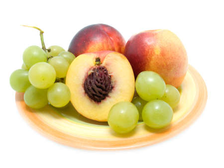Ripe peaches  and fresh grapes on a plate over white photo