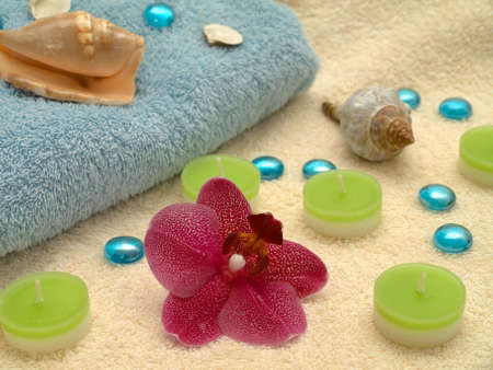 destress: Spa or health farm setting. Towel, candles and orchid. Stock Photo