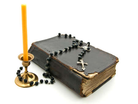 black gods: Old Bible with  candle in  bronze candlestick, cross and beads on white background