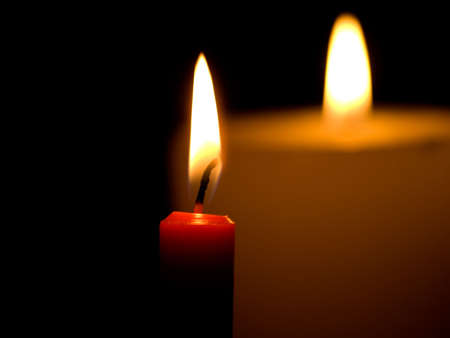 Two candles flaming in the dark  photo