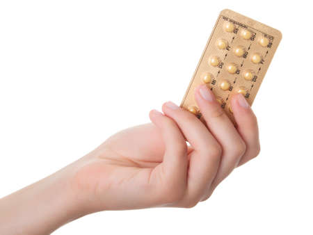 birth prevention: tablets (Birth Control Pills) in the hand, isolated on white background