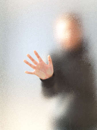 Silhouette of a girl through frosted glass  photo