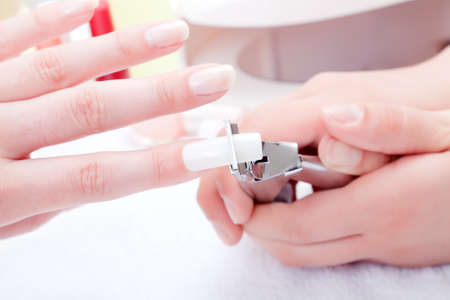 Manicurist trimming nail extensions on clients fingers  Archivio Fotografico