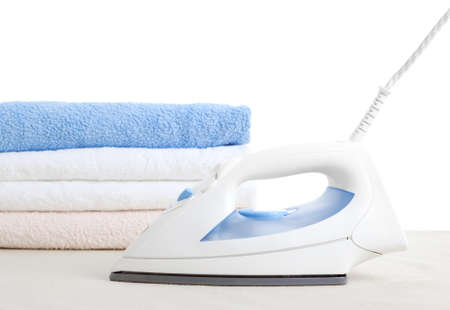 electric iron and towels, on white background  photo