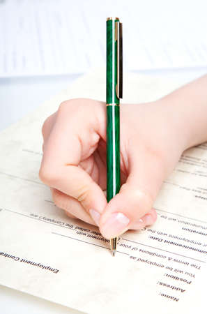 hand with pen over document  photo