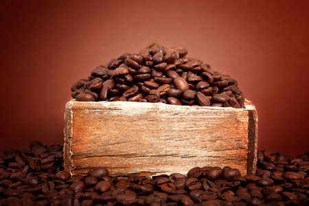 coffee crop: coffee beans in the old box, on brown background Stock Photo