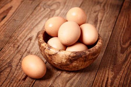 木製の背景に新鮮な茶色の卵