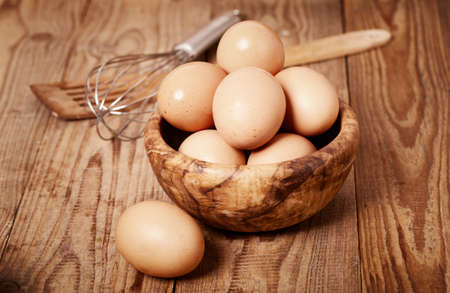 fresh brown eggs with egg whisk on wooden background photo