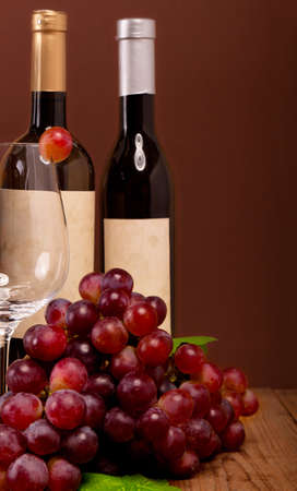 red grapes with wine bottles on brown background photo