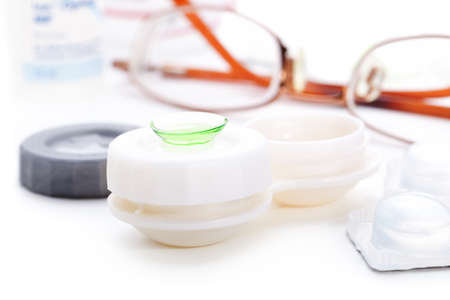 myopia: Close-up of green contact lenses in container with solution.   Stock Photo