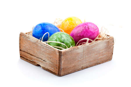 colored Easter eggs in the old box with straw photo
