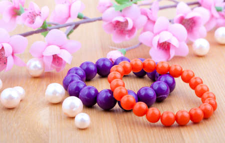 armlet: multi color coral bangles and artificial pearls, with pink flower on wooden background Stock Photo