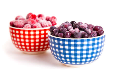 frozen raspberries and bilberries in the bowl, on a white background photo