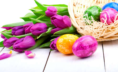 Easter eggs and bouquet tulips, on white wooden photo