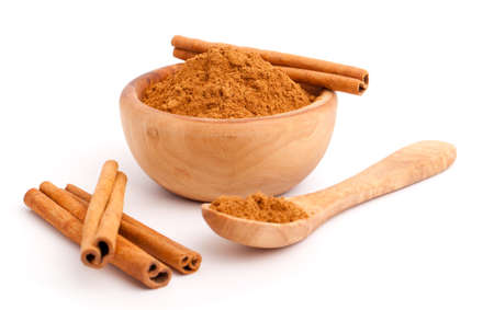 stick of cinnamon: powder of cinnamon in wooden bowl with spoon andCinnamon sticks Stock Photo