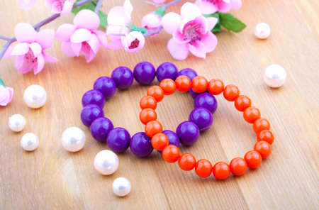 multi color coral bangles and artificial pearls, with pink flower on wooden background photo