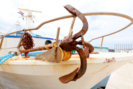 Closeup of old metal anchor on fishing boat photo