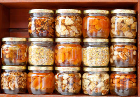 colorful honey with fruit and nuts in the jar, on a market in croatia. photo