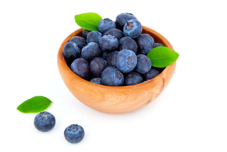 fresh blueberry in a wooden bowl with leaves, over a white background. photo