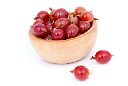 grosella: grosellas rojas frescas en un recipiente de madera, sobre un fondo blanco. Foto de archivo