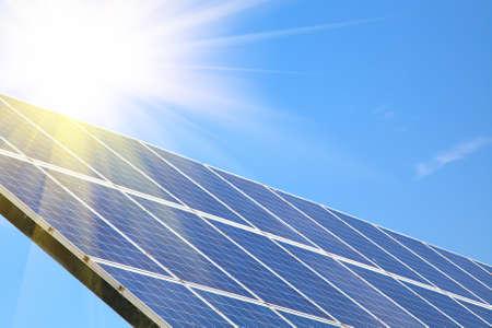 against the sun: Solar panel against blue sky with sun Stock Photo