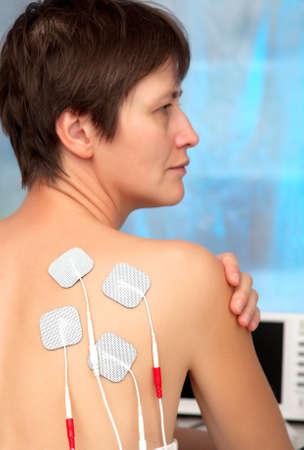 nervios: electrodos del dispositivo decenas de espalda de la mujer, decenas terapia, estimulación nerviosa Foto de archivo