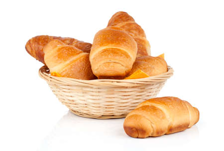 Fresh and tasty croissant in a straw basket, isolated on the white background