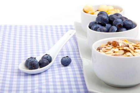 Serviette: ar�ndanos frescos en cuchara de porcelana blanca con taz�n de copos de ma�z, sobre servilleta