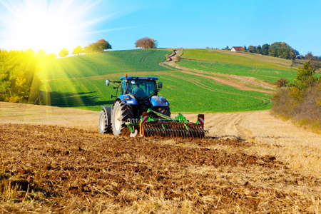 Tractor plows a field in the spring, with sunlight Stock Photo - 16574606