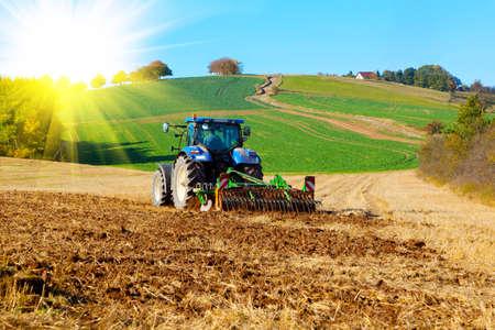 Traktor pflügt ein Feld im Frühjahr mit Sonnenlicht